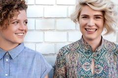 笑年轻女同性恋的夫妇,当一起时站立外面 库存图片