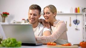 笑年轻的夫妇寻找在网站上的食物食谱和,厨房新手 库存图片