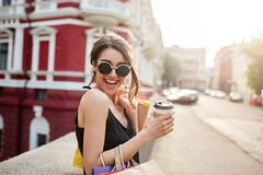 笑年轻美丽的深色头发的白种人的妇女画象太阳镜和黑礼服的,度过假期 免版税库存图片