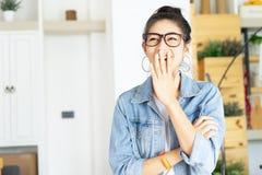 笑快乐的亚裔的妇女画象在家盖她的嘴用手反对办公室 免版税库存照片
