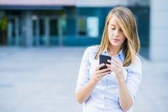 笑快乐的少妇画象谈话在智能手机和户外 库存图片