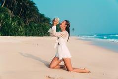 笑快乐的美丽的愉快的女孩,当站立在海滩,以森林为背景和时 免版税图库摄影