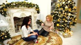 笑快活的女孩获得乐趣和坐地板在有欢乐壁炉的明亮的客厅装饰与 影视素材
