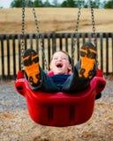 笑愉快的孩子,当摇摆时 免版税库存照片