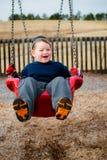 笑愉快的孩子,当摇摆时 免版税库存图片