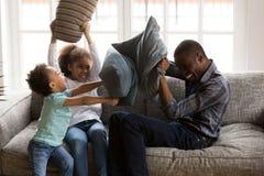 笑愉快的小孩享受与非洲的枕头战 图库摄影