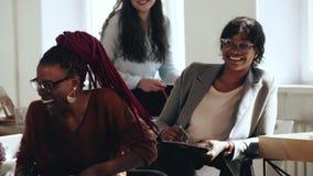 笑愉快的激动的创造性的非洲的女商人,获得乐趣在与不同种族的同事的现代办公室会谈上 股票录像