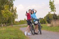 笑愉快的运动的骑自行车的人的夫妇显示标志的Thums和  免版税库存图片