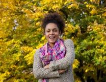 笑户外在秋天的年轻非裔美国人的妇女 免版税库存照片