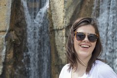 笑有瀑布背景的妇女 库存图片