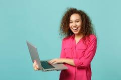 笑桃红色便服的非洲女孩画象使用膝上型计算机在蓝色绿松石墙壁上隔绝的个人计算机计算机 图库摄影