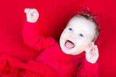 笑演奏女婴在一条红色毯子下 免版税库存图片