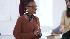 笑特写镜头愉快的激动的年轻非洲女性的上司,聊天对作会议报告的观众在现代办公室 股票视频