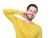 笑用在头发的手的一个年轻人的画象 免版税库存图片