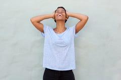 笑用在头后的手的无忧无虑的年轻黑人妇女 图库摄影