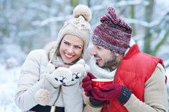 笑用茶的夫妇在冬天 免版税库存照片