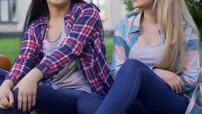 笑白肤金发和深色的女孩坐草坪,谈话和,学院朋友 股票录像