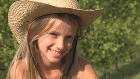 笑的儿童放松室外在草,在自然女孩画象的愉快的孩子面孔 免版税库存图片
