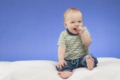 笑的八个月的男婴,坐白色毯子,演播室射击,隔绝在蓝色背景 免版税库存图片