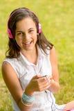 笑的十几岁的女孩听音乐坐的草 库存照片