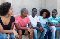 笑的和谈的小组非裔美国人的男人和妇女 库存图片
