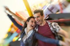 笑的夫妇在骑马弗累斯大转轮享用 免版税库存图片