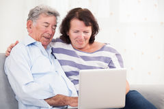 笑的女儿和的父亲,当使用膝上型计算机时 库存图片