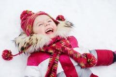 笑的女孩在雪说谎 免版税库存图片