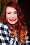 笑的女孩快乐的年轻画象红头发人长的头发红色唇膏蓝眼睛衬衣 免版税库存照片