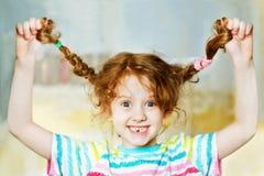 笑的女孩用手脱掉她的猪尾并且显示她teeths C 库存照片
