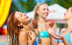 笑的女孩获得乐趣在夏天阵雨下 免版税库存照片