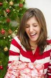 笑的女孩,当接受圣诞节礼物时 免版税库存照片