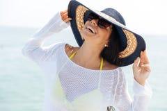 笑的妇女佩带的海滩帽子和比基尼泳装的画象 免版税库存图片