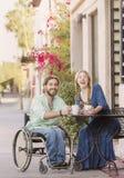 笑的妇女和人轮椅的户外 库存图片