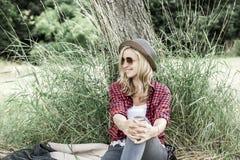 年轻笑的妇女坐草甸 库存照片