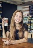笑的妇女拿着一杯咖啡 免版税库存照片
