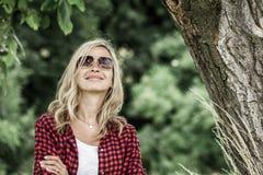 年轻笑的妇女本质上在树前的 库存照片