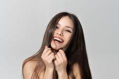 笑的妇女用头发盖她的面孔 免版税图库摄影