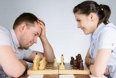 笑的妇女,当下棋反对一个沉思的人时 免版税库存图片