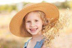 笑的孩子女孩佩带的帽子户外 免版税图库摄影
