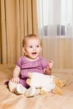 笑的小女孩坐与玩具的床 免版税库存照片