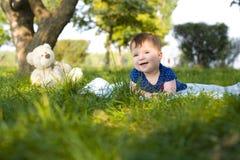 笑的小女孩坐草在夏天 图库摄影