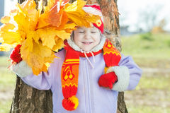 笑的小女孩对负黄色与橙色秋叶束起手中室外画象 库存图片