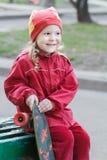 笑的小女孩拿着滑板和坐绿色木长凳 库存图片