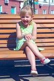 笑的小女孩,当坐长凳在城市公园时 正面儿童` s情感 免版税图库摄影