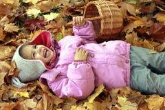 笑的小女孩,当说谎在地面上时 免版税图库摄影