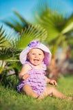 笑的小女孩,特写镜头画象 一个愉快的女孩的画象在度假 紫色的一个女孩坐草坪 免版税图库摄影
