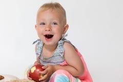 笑的小孩女孩拿着红色苹果 免版税库存图片
