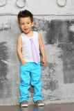 笑的小男孩站立近的墙壁 免版税库存图片