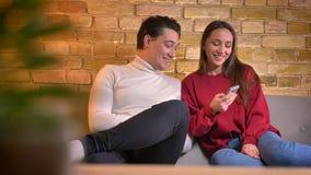笑的年轻白种人夫妇坐沙发观看入智能手机和谈话互相在家庭环境 股票录像